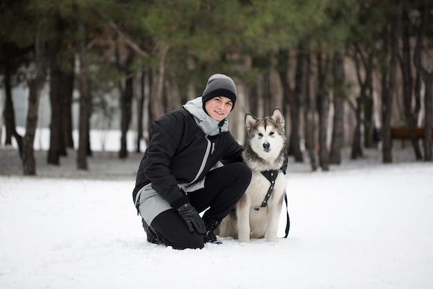 Uomo felice nella foresta invernale con un cane. per giocare con il cane siberian husky.