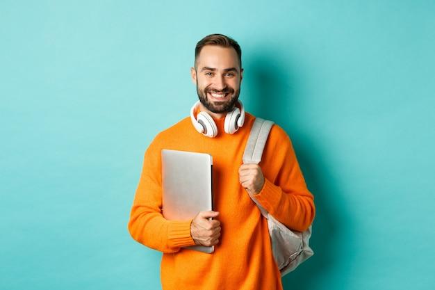 Uomo felice con zaino e cuffie, tenendo laptop e sorridente, andando a lavorare, in piedi su sfondo turchese.