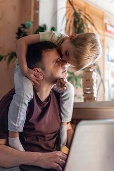 Uomo felice con i bambini che utilizzano laptop e auricolari durante il lavoro a casa, la vita in quarantena