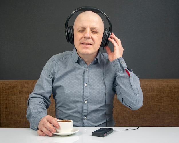 L'uomo felice con una tazza di caffè in cuffie portatili ascolta musica utilizzando un lettore.