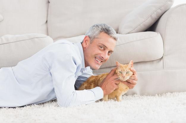 Uomo felice con cane sdraiato sul tappeto