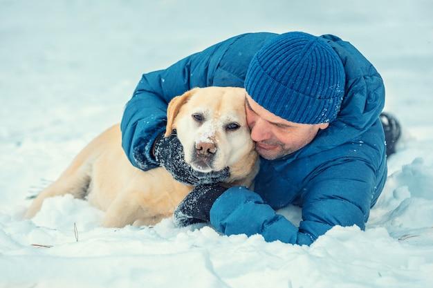 Un uomo felice con un cane labrador retriever sdraiato nella neve in inverno. uomo che abbraccia il cane