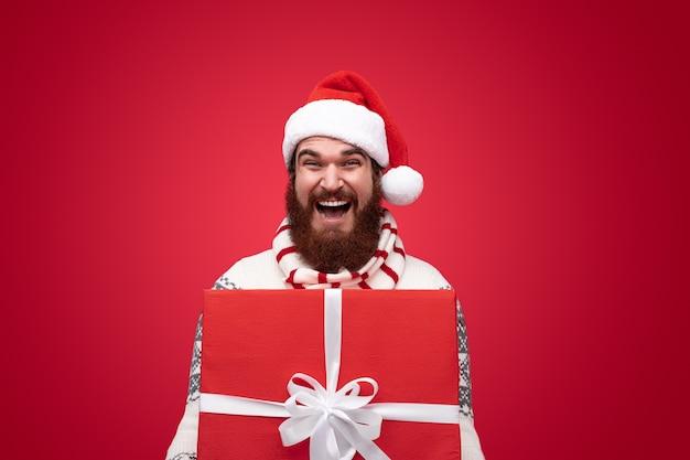 Uomo felice con la barba lunga che fa una sorpresa di natale
