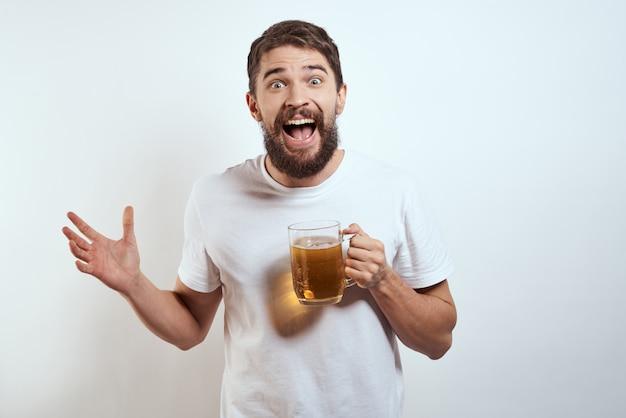 Uomo felice con una tazza di birra alcolica nelle sue mani