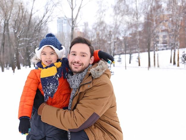 Uomo felice con il figlio nel parco innevato in vacanza invernale