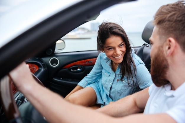 Felice l'uomo e la donna alla guida di auto cabriolet all'aperto
