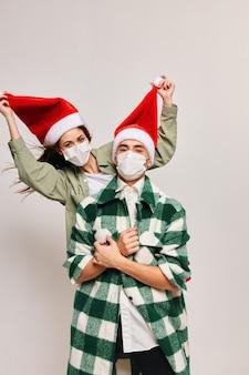 Felice uomo e donna in vacanza con la famiglia maschera medica di natale.