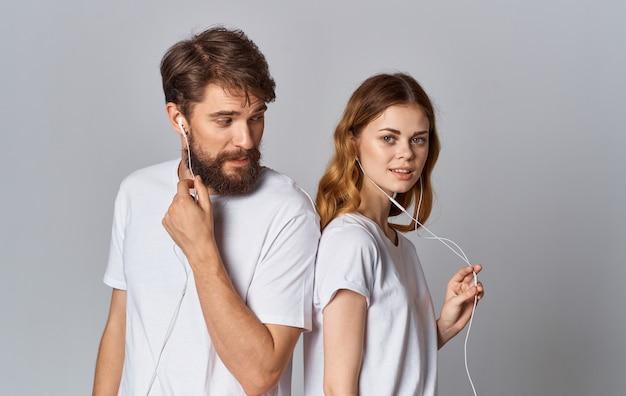 Uomo e donna felici in cuffie su sfondo grigio guardano e stanno con le spalle l'un l'altro