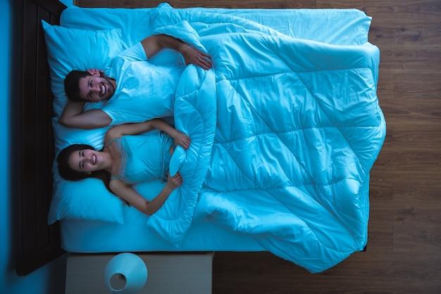 L'uomo felice e una donna sdraiata sul letto. serale notturno. vista dall'alto