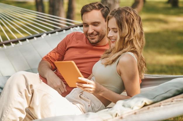 Uomo e donna felici che sembrano interessati al tablet
