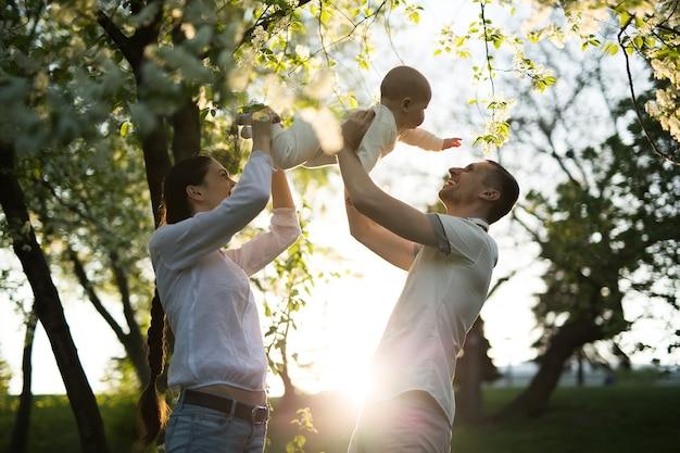 Uomo e donna felici che giocano con il bambino all'aperto