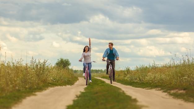 L'uomo e la donna felici che vanno in bicicletta in un campo