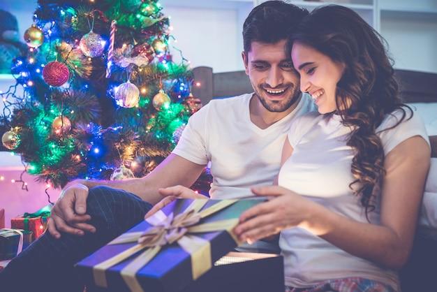 L'uomo felice e una donna disimballano la confezione regalo vicino all'albero di natale