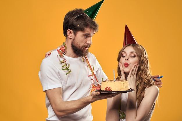 Felice l'uomo e la donna con la torta di compleanno festa di compleanno tappo e sfondo giallo