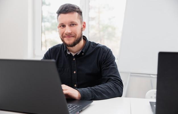 Uomo felice che lavora al computer portatile in ufficio