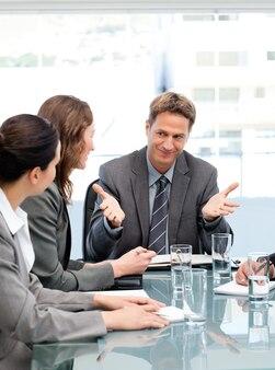 Responsabile felice che parla con sua squadra che si siede ad un tavolo