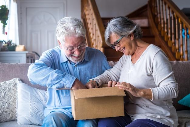Felice coppia di famiglia anziana matura che disimballa la scatola di cartone, soddisfatta dell'acquisto di un negozio online o di un regalo inaspettato, entusiasta del servizio di spedizione di consegna veloce, esperienza di acquisto positiva.