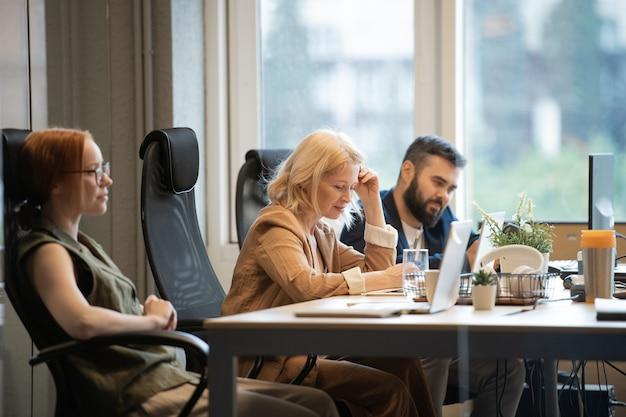 Felice imprenditrice matura seduto alla scrivania tra due giovani colleghi e guardando attraverso le informazioni davanti al computer portatile