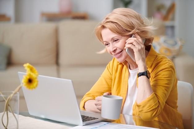Felice imprenditrice matura con tazza e telefono cellulare che consulta uno dei clienti mentre si lavora a distanza durante l'isolamento domestico