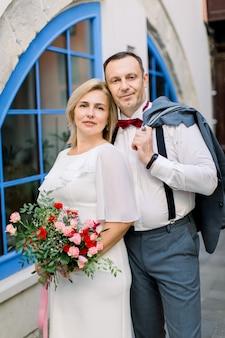 Felice coppia matura, abbracciata all'aperto in città, in posa vicino a bellissime finestre blu vintage
