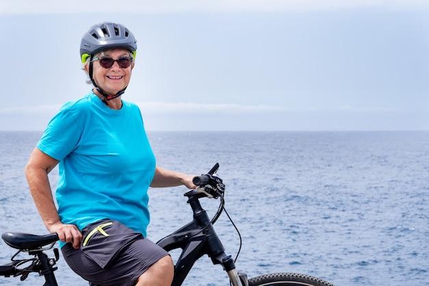 Felice donna ciclista matura che gode di una sana attività in mare con la sua bici elettrica. in piedi sulla scogliera