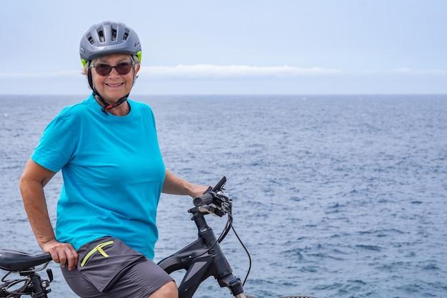 Felice donna ciclista matura che si gode una sana attività in mare con la sua bici elettrica