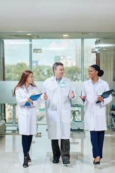 Medico maturo felice che cammina attraverso il corridoio della clinica e parla con i giovani stagisti femminili sorridenti