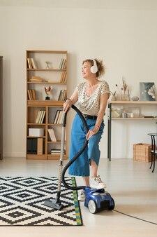 Felice femmina matura in homewear utilizzando l'aspirapolvere mentre pulisce il soggiorno e canta la sua musica preferita in cuffia