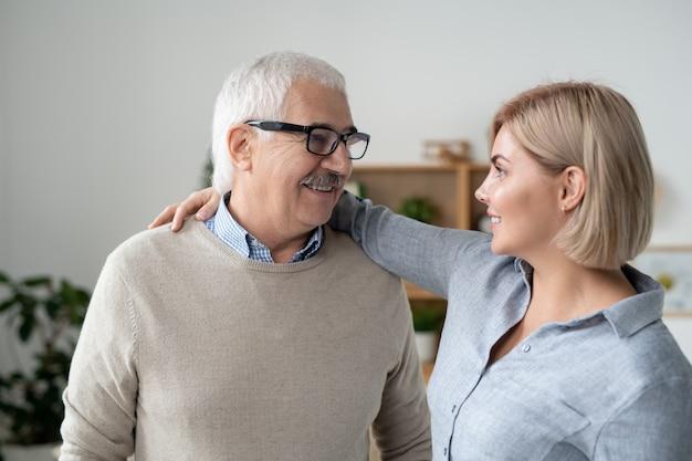 Felice maturo uomo dai capelli grigi in occhiali e abbigliamento casual e la sua giovane figlia bionda che si abbracciano e si guardano
