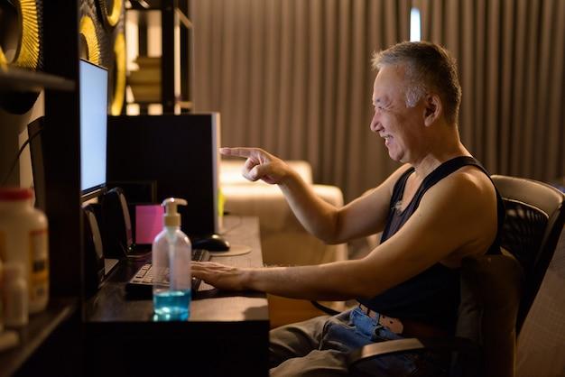 Video giapponese maturo felice dell'uomo che chiama con il computer a casa