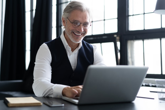 Felice uomo maturo in tuta completa utilizzando laptop mentre si lavora in un ufficio moderno