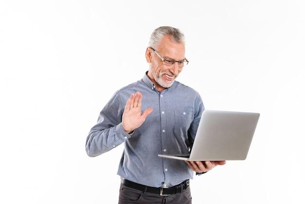 Uomo maturo felice che fa videocall con il computer portatile isolato