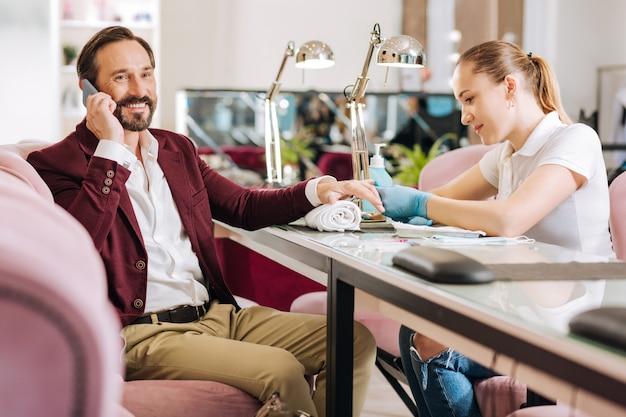 Uomo maturo felice che parla sul telefono e donna che fa manicure
