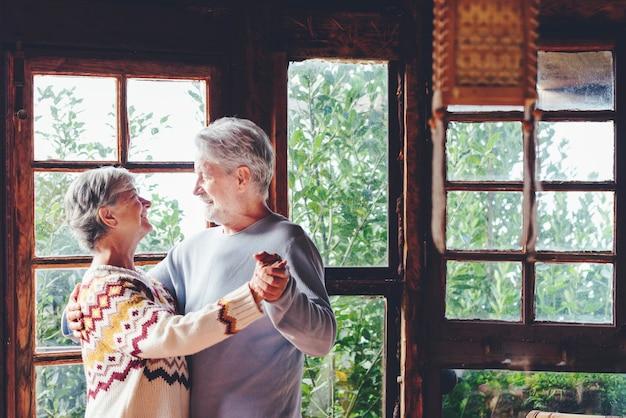 L'uomo e la donna maturi felici ballano a casa godendosi l'amore. la relazione di persone anziane si diverte al coperto nel tempo libero danzante attivo. le coppie anziane sorridono e si guardano