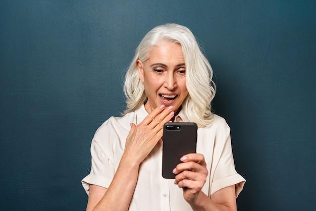 Donna anziana matura felice che per mezzo del telefono cellulare