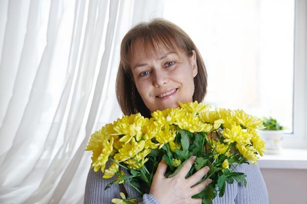 Donna matura felice che tiene una bracciata di fiori gialli