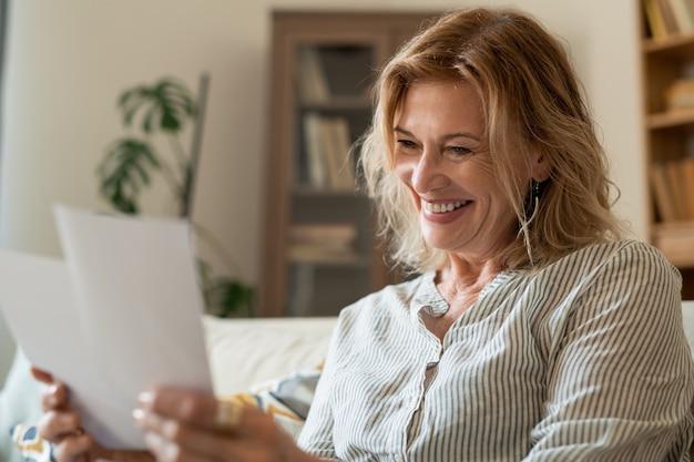 Donna matura felice che ride mentre guarda le foto di famiglia mentre si resta a casa nel fine settimana o si rilassa la sera dopo la giornata lavorativa