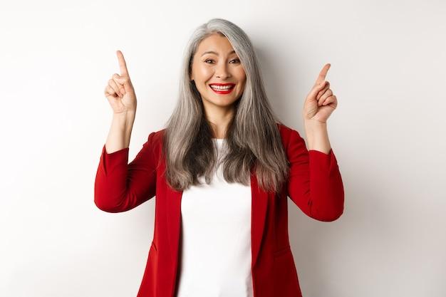 Felice donna matura in giacca rossa e trucco, sorridendo e mostrando pubblicità in alto, puntando le dita verso il logo, sfondo bianco.