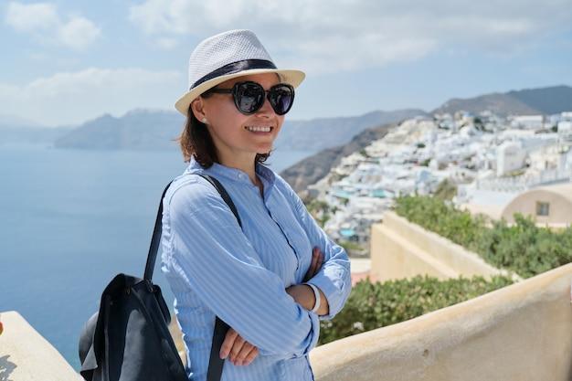 Turista della donna matura felice che viaggia sulla famosa isola di santorini