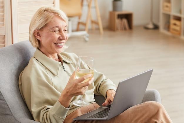 Felice donna matura utilizzando il computer portatile e bere vino mentre si riposa sulla poltrona nel soggiorno di casa