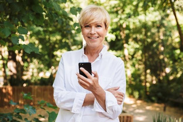Donna matura felice che per mezzo del telefono cellulare