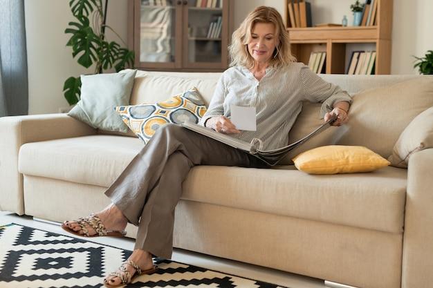 Felice donna matura con capelli biondi che si distende sul divano in soggiorno e guardando attraverso album con foto di famiglia mentre si resta a casa