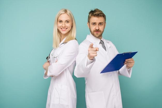 Felice team medico di medici, uomo che punta alla donna anteriore e sorridente, isolato su uno spazio blu