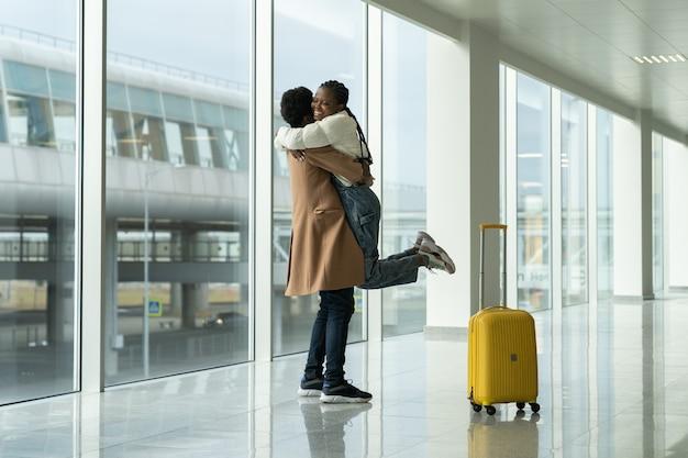 Felice incontro all'aeroporto, l'uomo africano ha incontrato e abbracciato la donna dopo l'arrivo nel terminal moderno vuoto