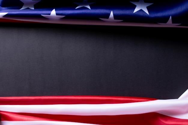 Buon memorial day o independence day. bandiere americane contro uno sfondo di carta nera.