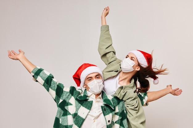 Uomini e donne felici in cappelli festivi gesticolano con le mani su uno sfondo chiaro