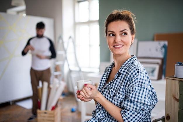 Felice coppia di adulti di mezza età che dipinge mobili in casa, trasloco e concetto fai da te.