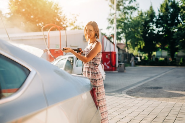 Felice donna di mezza età che lava l'auto alla stazione di autolavaggio utilizzando una macchina per l'acqua ad alta pressione