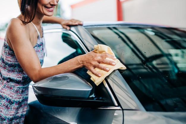 Felice mezza età donna lavaggio auto la sera alla stazione di lavaggio auto.