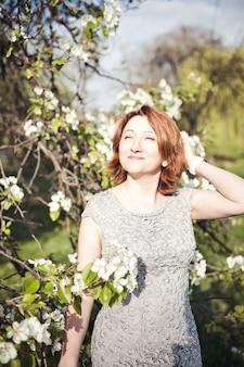 Felice donna armena di mezza età in un abito elegante sotto l'albero in fiore
